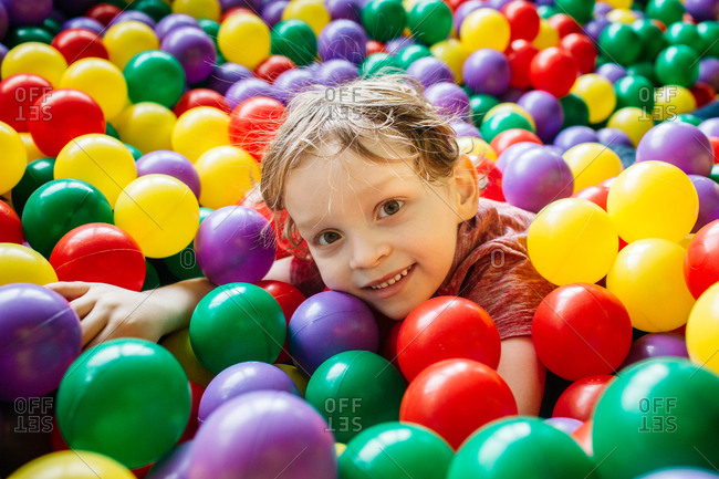 Smiling child having fun with colorful balls at indoor playground