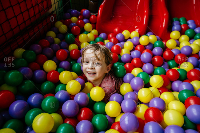 Smiling child diving in a pool of balls at indoor playground