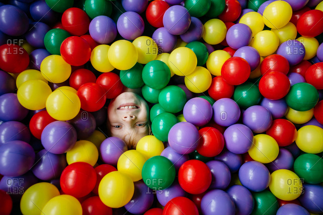 Close up of a happy child's face dived in a pool of colorful balls