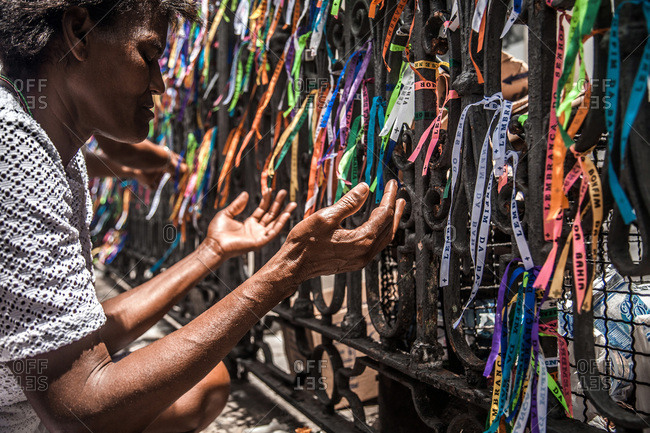 Salvador, Brazil - January 15, 2009: Senior woman kneeling in front of a railing covered in prayer ribbons
