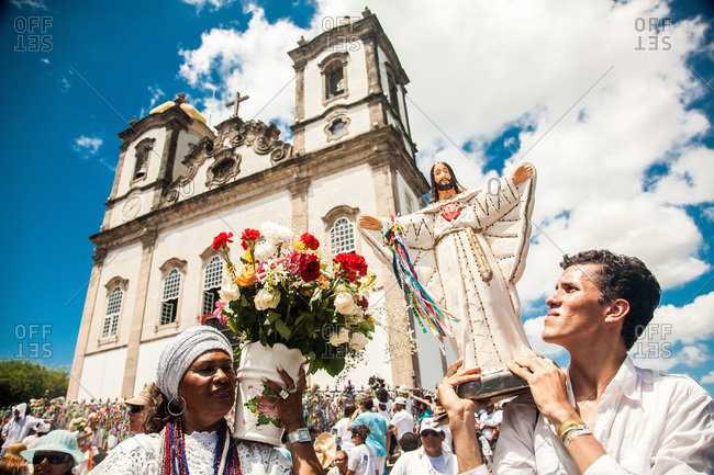 Salvador, Brazil - January 15, 2009: Man holding a statue of Jesus in front of the Bonfim Church