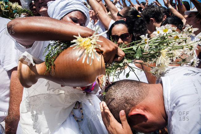 Salvador, Brazil - January 15, 2009: Woman pouring water from a vase over a man's head