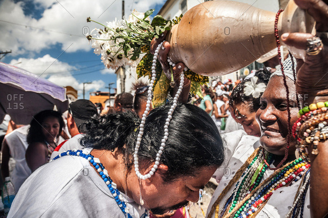 Salvador, Brazil - January 15, 2009: Woman pouring water from a flower bouquet over a man's head