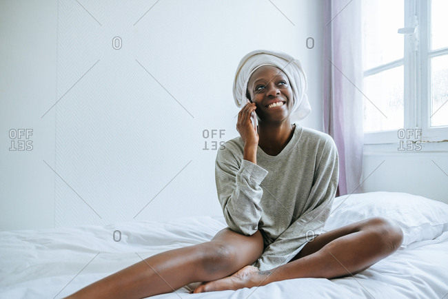 Young woman in her room talking on mobile phone with towel on her head