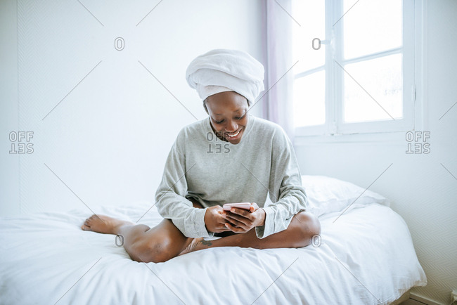 Young woman in her bedroom using mobile phone with towel on her head