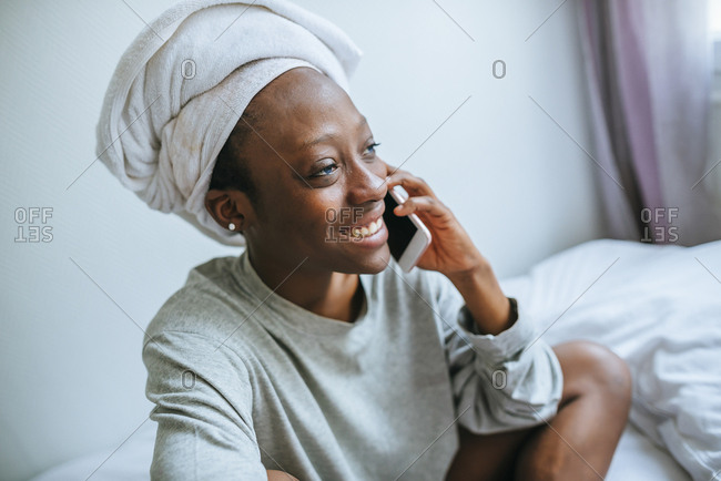 Woman in her room talking on mobile phone with towel on her head