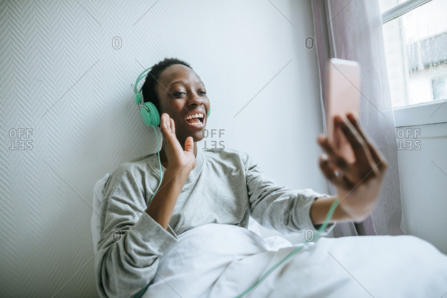 Young woman in her room doing a video call with a smart phone