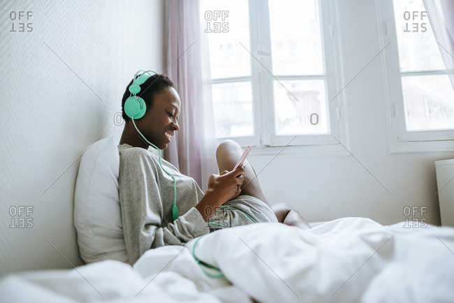 Young woman in her room with headphones and mobile phone