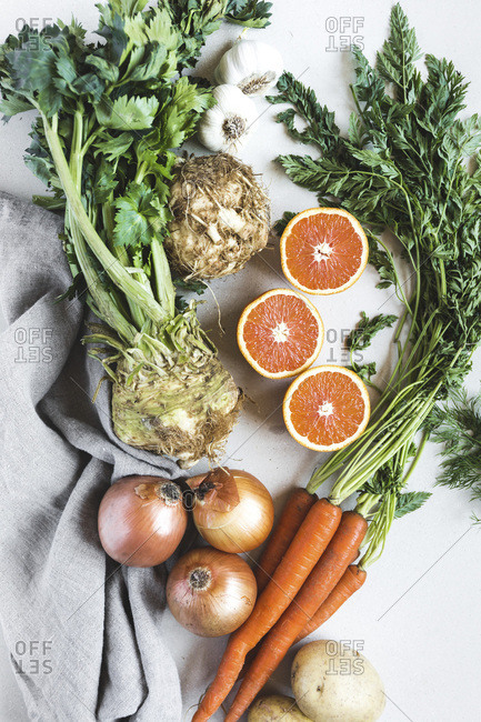 celery root, sliced oranges, carrots, and onions are photographed from the top view