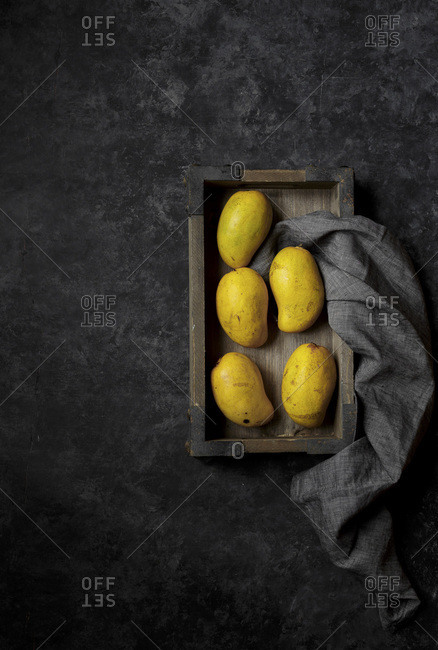 Mangoes in a wooden tray
