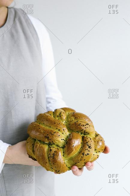 Girl in grey apron holding bread