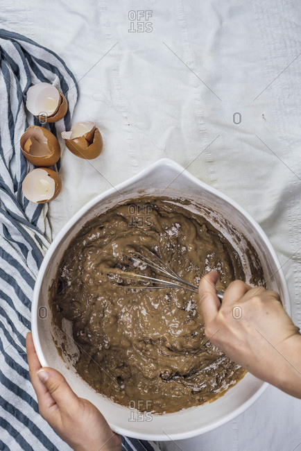 A woman mixing a cake batter in a large bowl photographed from top view Egg shells are on the side