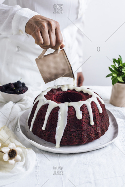 A woman with a white shirt pouring a white glaze on a red velvet bundt cake photographed from front view