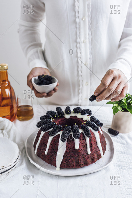 A woman with white shirt topping a red velvet bundt cake with black mulberries photographed from front view