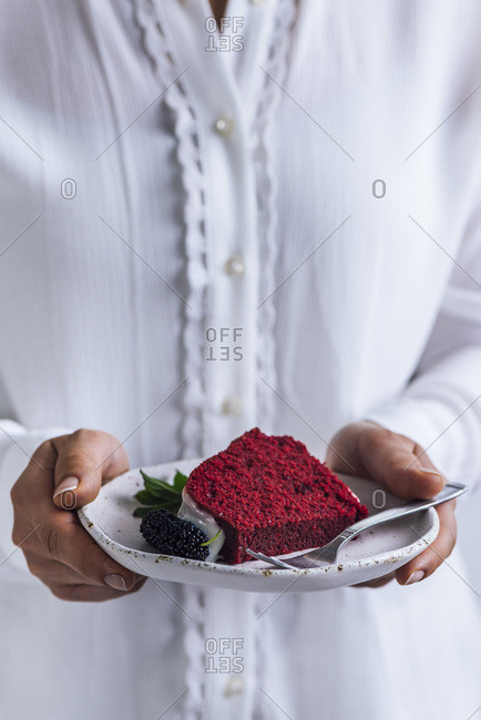 A woman with white shirt holding a slice of red velvet bundt cake with white glaze, a mulberry and mint garnish in a ceramic white plate with a fork on the side