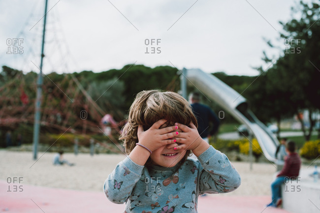 Girl playing hide-and-seek on a playground