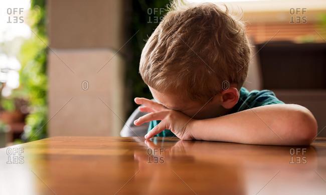 Boy wiping his eyes at table