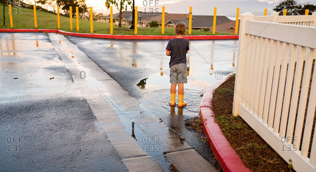 Boy in galoshes looking over neighborhood