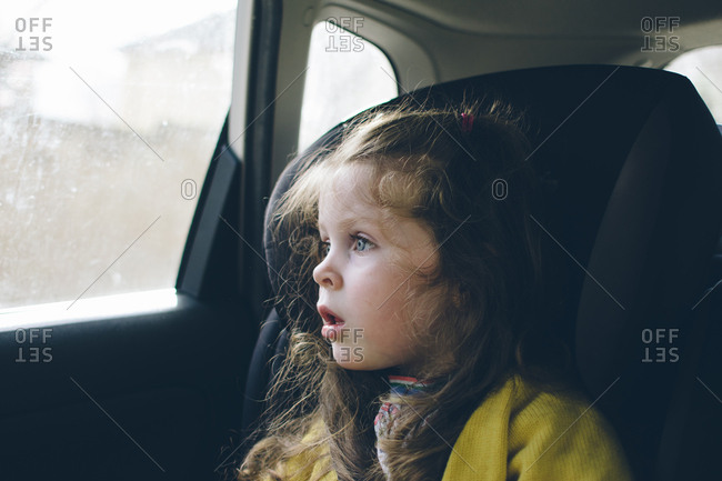 Girl staring in wonder out car window