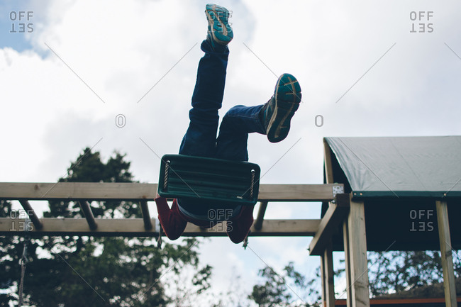 Child swinging high in playground