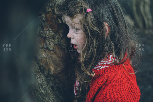 Girl leaning against a tree in forest