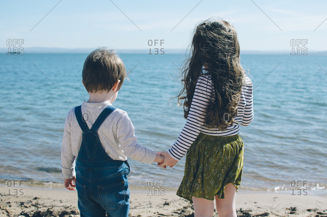 Girl holding boy's hand on a beach