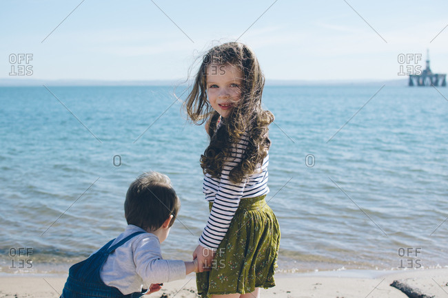 Girl holding a boy's hand on beach