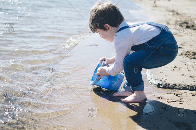 Boy scooping ocean water with bucket