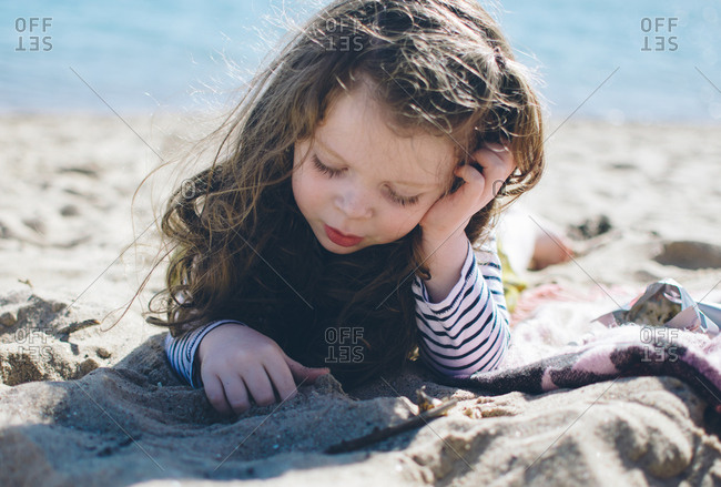 Contemplative girl lying on beach