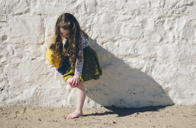 Girl brushing off soles of her feet