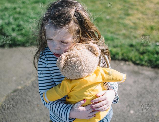 Girl holding teddy bear for comfort