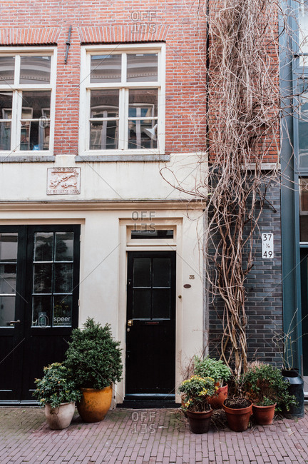 Amsterdam, Holland - February 17, 2014: Doorway of brick building with potted plants
