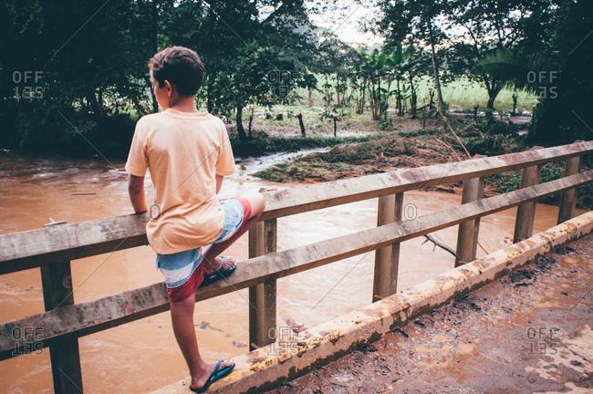 Boy facing away on muddy bridge