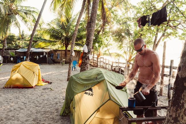 Samara, Costa Rica - October 29, 2012: Man cooking at campground on beach