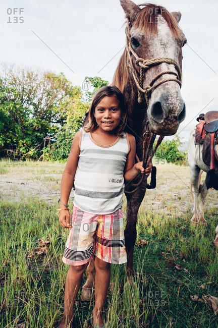 Samara, Costa Rica - October 29, 2012: Young costa Rican boy with horse