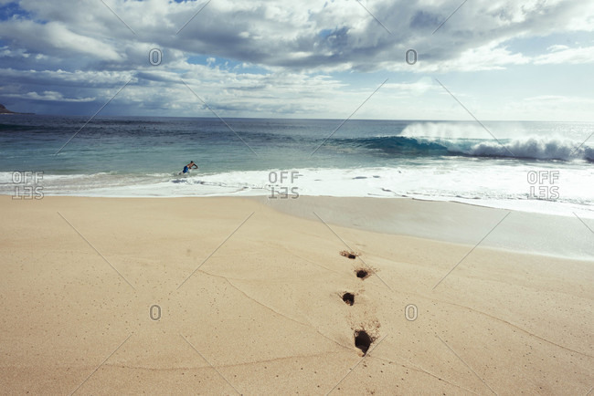 Man diving in water with footprints in sand