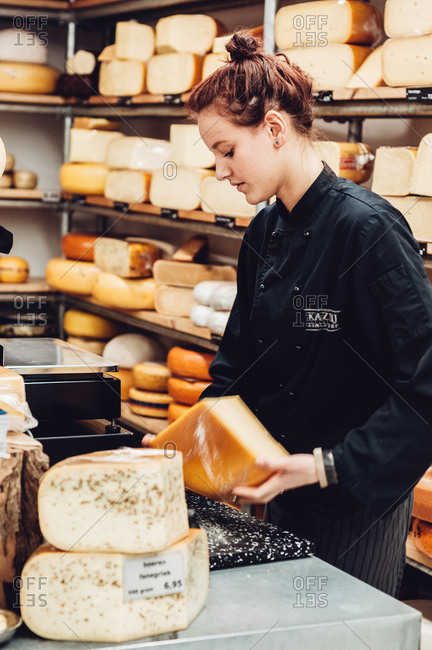 Utrecht, Netherlands - February 14, 2014: Girl cutting cheese in cheese store