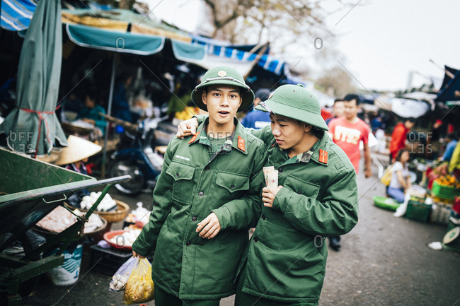 Hue, Vietnam - January 13, 2017: Two young men in army uniforms walk through the market