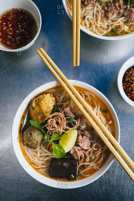 A bowl of Bun Bo Hue with beef, crab balls, blood sausage and herbs, a local specialty in Hue, Vietnam