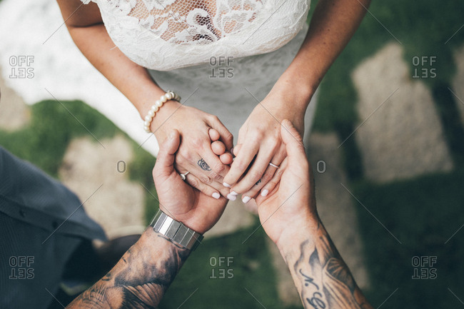 A tattooed husband and wife exchange wedding rings during a garden ceremony