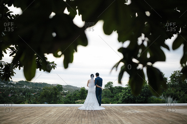 A young married couple looks out over a tropical island in Thailand