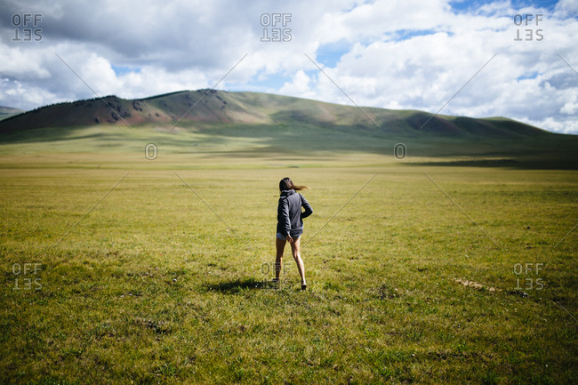 A young woman walks into the vast open plains of northern Mongolia