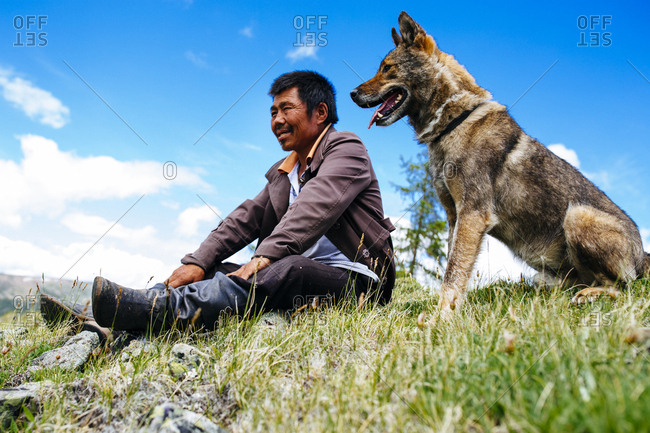 Northern Mongolia  - July 13, 2016: A man sits with his dog on a hilltop overlooking the vast plains and mountains