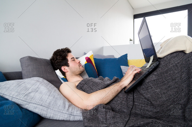 Man using laptop while lounging