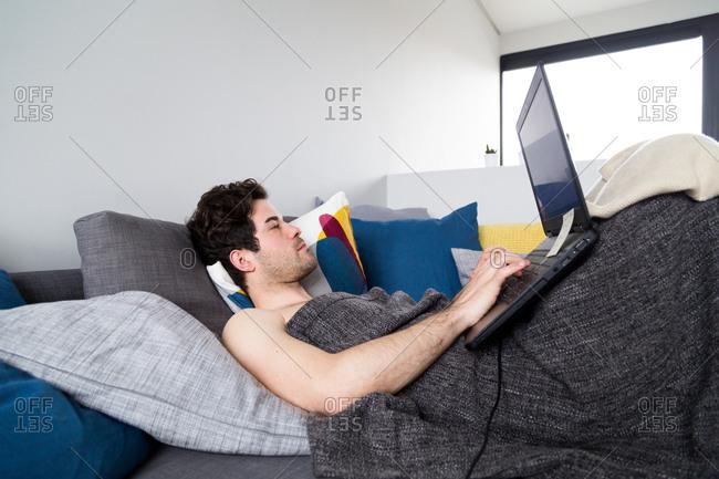 Man using laptop while lounging