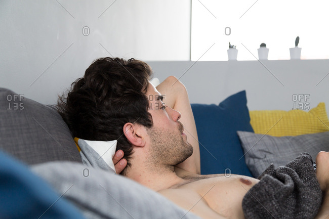 Man laying down shirtless on couch