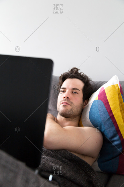 Shirtless man using laptop while laying down