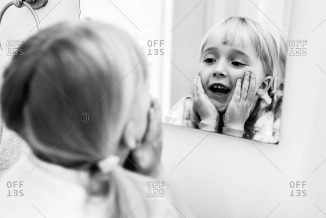 Girl looking in the mirror in black and white