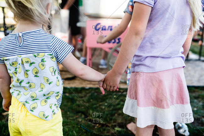 Sisters holding hands while waiting in line at a carnival