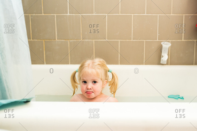 Toddler girl with pigtails taking a bath